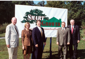 Smart Growth founders in front of a log banner